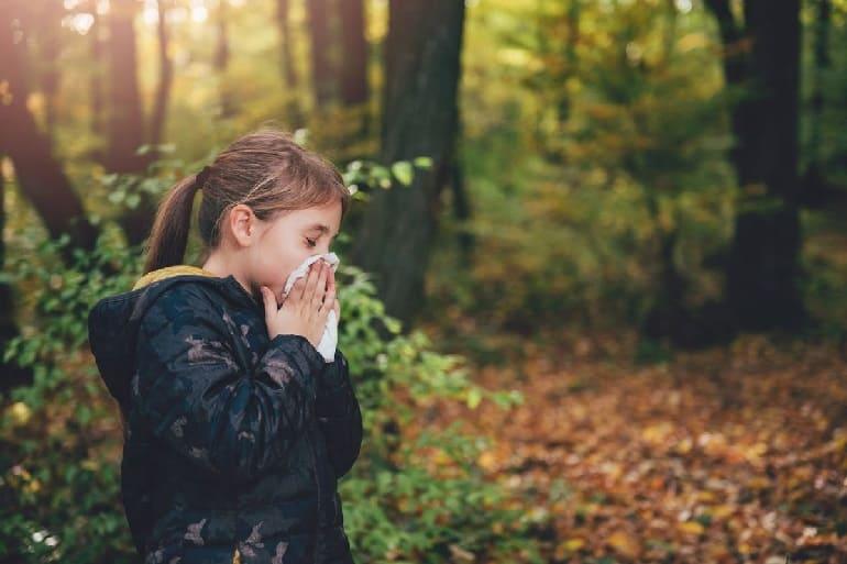 Девочка чихает в лесу
